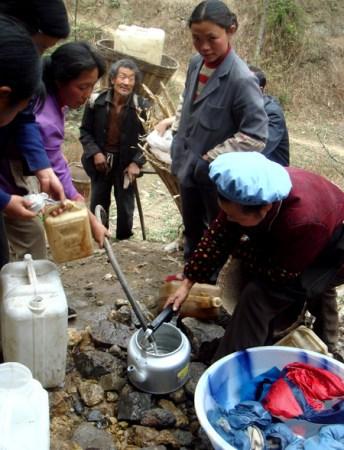 村民们用水桶或自制的塑料袋来盛水