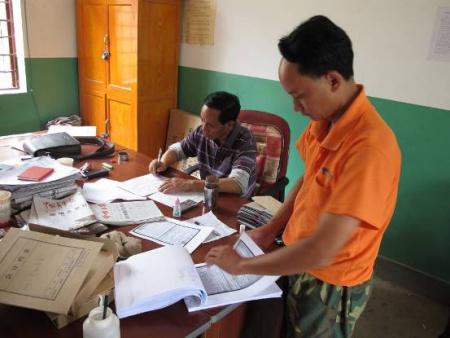 环州乡政府办公室工作人员整理项目农户申请资料
