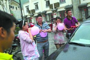 年轻人吹着彩色气球,准备装点花车。