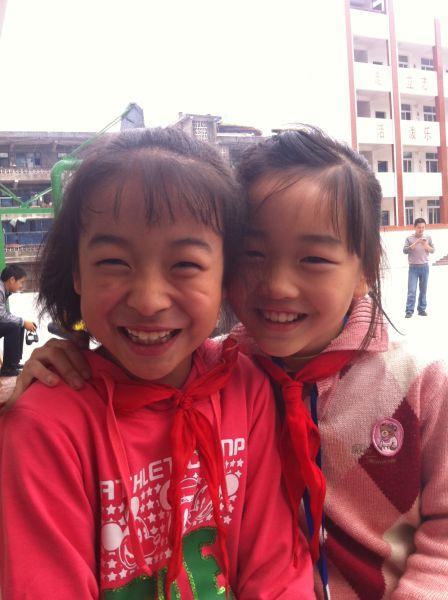 曾口小学四年级苟凤琳、刘湘湘收到助学金后开心地笑了