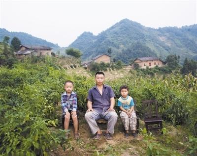 双龙镇,程孝林和两个孩子在菜地里。程孝林的妻子在外打工。