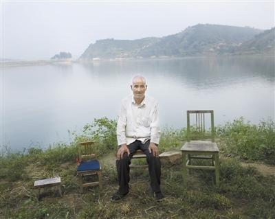 林皋镇,66岁的焦栓成坐在家附近的湖边。他的3个孩子外出打工。