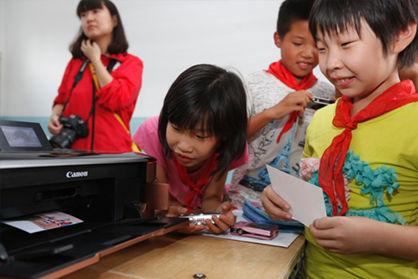 孩子们将自己所拍摄的照片打印出来制作文化交流卡