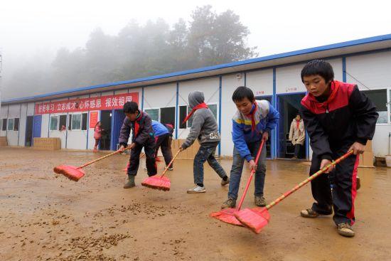 高年级的学生正清扫操场上的石子