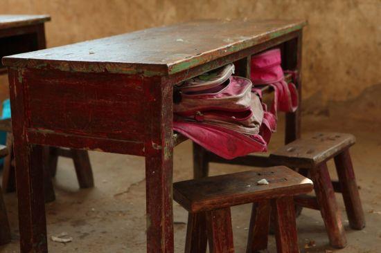教室中老旧的桌椅和孩子们破洞的书包