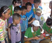 志愿者们在教授小朋友电脑知识